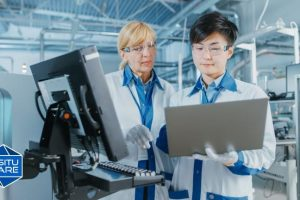 Two employees using machines in factory